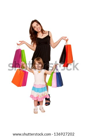 Family shopping. Two sisters, a teenager and a little girl holding up shopping bags and smiling. Holidays and gifts concept. Isolated on white background - stock photo
