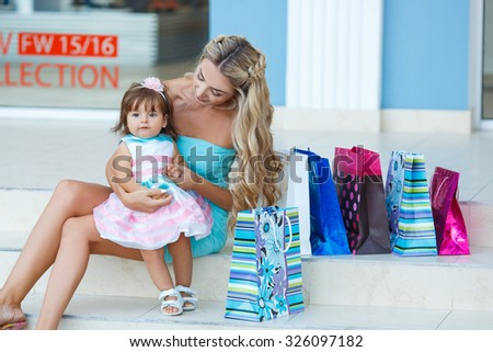 Family shopping. Young mother and her daughter doing shopping together. Woman with child on shopping in shopping mall with bags. Mother with baby girl with shopping bags with mall on background. - stock photo