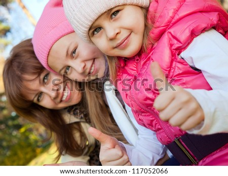 Family showing their thumb up at autumn - stock photo
