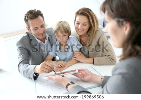 Family signing home purchase contract on tablet - stock photo