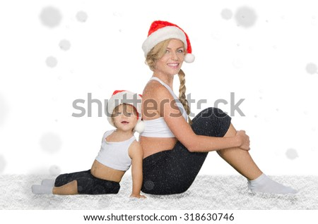 family sits in snow in Santa hats and clothing for fitness - stock photo