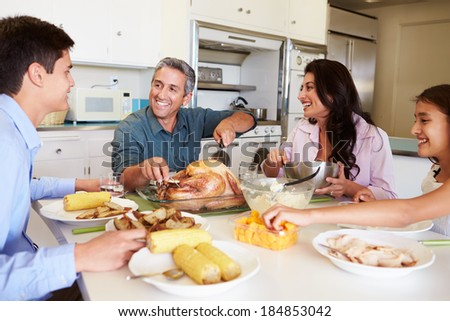Family Sitting Around Table At Home Eating Meal - stock photo