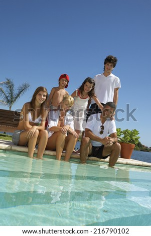 Family sitting by the pool. - stock photo