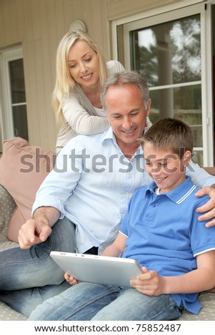 Family sitting, in couch with electronic tablet