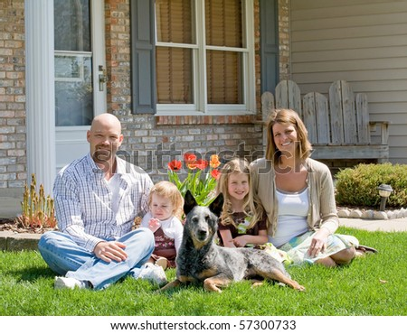 Family Sitting in Front of Their Home - stock photo