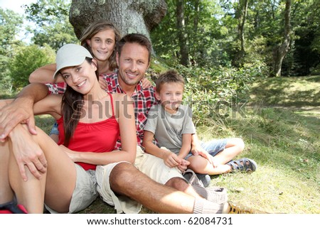 Family sitting in nature on a hiking day - stock photo