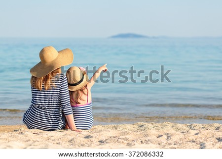 Family sitting next to each other at the beach while daughter is pointing with her hand - stock photo