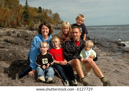 family sitting next to lake superior - stock photo