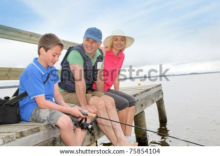 Family sitting on a pontoon with kid fishing - stock photo