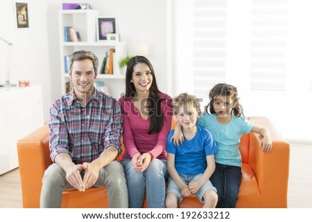 family sitting on a sofa in her living room