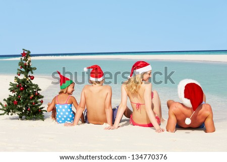 Family Sitting On Beach With Christmas Tree And Hats - stock photo