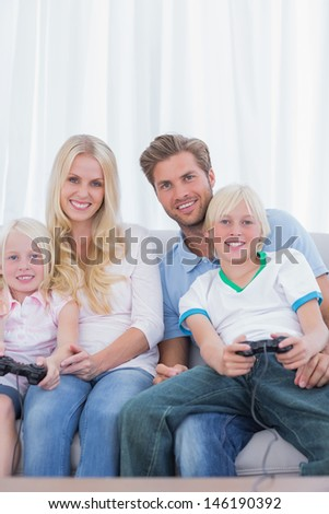 Family sitting on couch playing video games in the living room