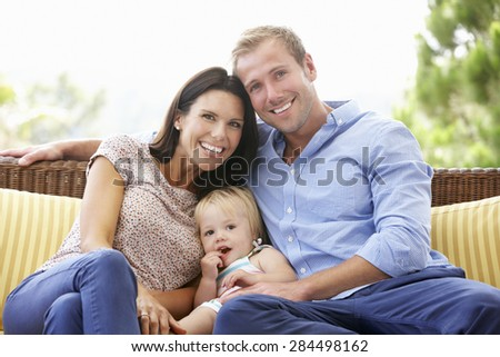 Family Sitting On Garden Seat Together - stock photo