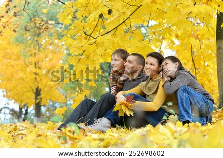 Family sitting on grass in autumn park - stock photo