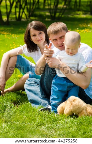 Family sitting on grass in the spring park