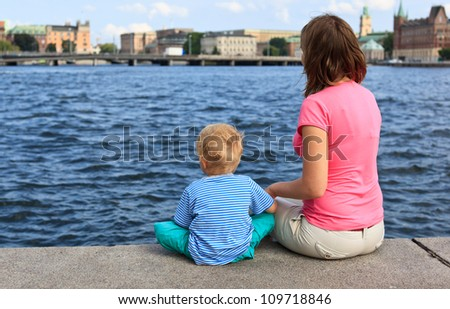 Family sitting on jetty - stock photo