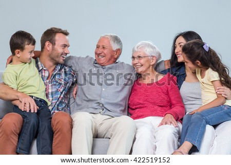 Family sitting on sofa and smiling in living room - stock photo