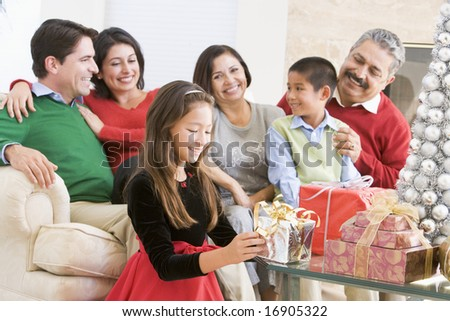 Family Sitting On Sofa In Front Of Christmas Presents,Young Girl Selecting A Gift - stock photo