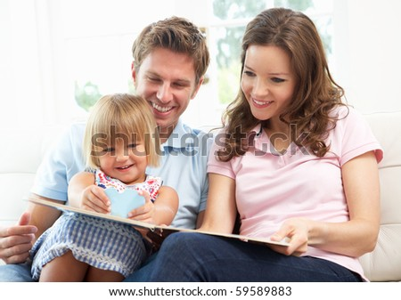 Family Sitting On Sofa Reading Book At Home - stock photo
