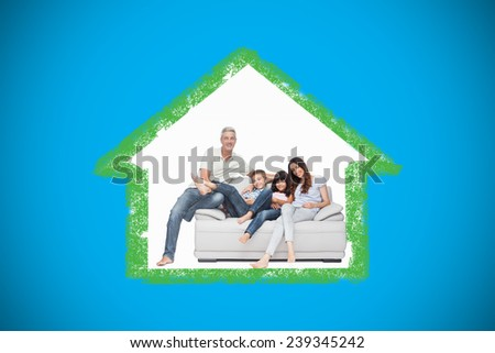 Family sitting on sofa smiling at camera against blue background with vignette