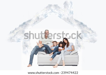 Family sitting on sofa smiling at camera against house outline in clouds - stock photo