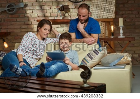 Family sitting on sofa together, little boy using tablet, playing. - stock photo