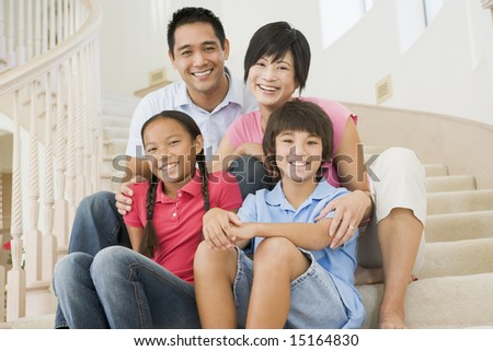 Family sitting on staircase smiling - stock photo