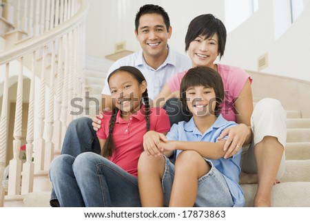 Family sitting on staircase smiling - stock photo