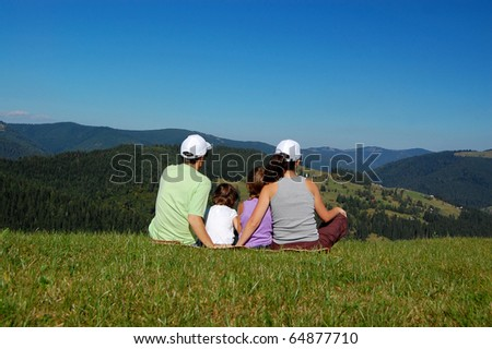 Family sitting on the grass and looking at the beautiful mountain view - stock photo