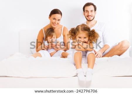 Family sitting on white bed in pajamas together - stock photo