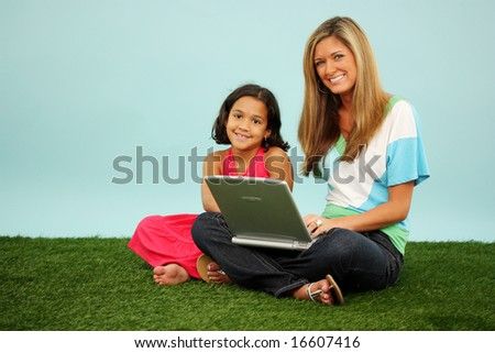 Family Sitting Together Outside In The Grass With Computer