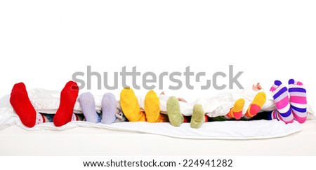 Family sleeping together. Feet of father, mother and four children in colorful knitted socks on white bed. Isolated on white background. Ready for your text - stock photo