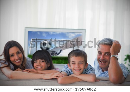 Family smiling at the camera with television - stock photo