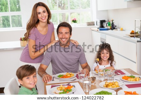 Family smiling at the dinner table in kitchen - stock photo