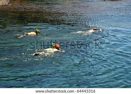 family snorkeling in a natural basin in Lanzarote