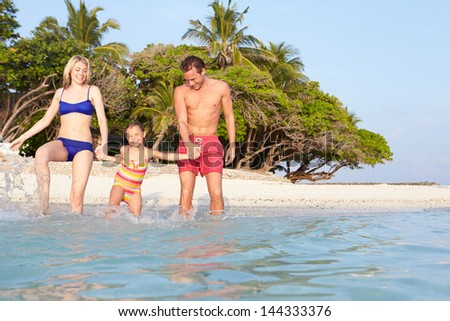 Family Splashing In The Sea On Tropical Beach Holiday - stock photo