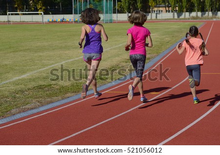 Family sport, active mother and kids running on stadium track, back view, training with children fitness concept
