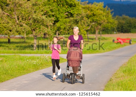 Family sport - mother and daughter jogging down a path with a baby stroller at a wonderful sunny day - stock photo