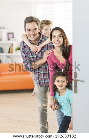 Family standing at front door to invite people at home - stock photo