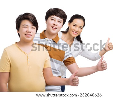 Family standing in a row and showing thumbs up - stock photo