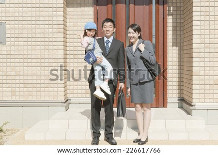 Family standing in front of the front door - stock photo