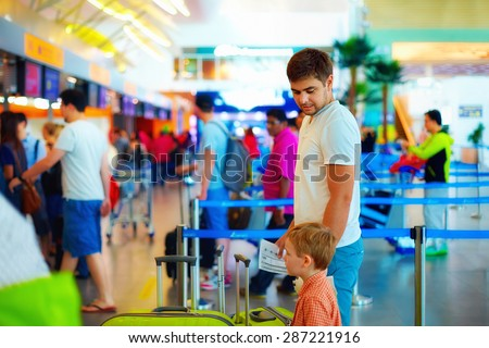 family standing in queue at passport control check in international airport - stock photo