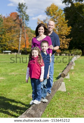 Family standing on a log during the fall - stock photo