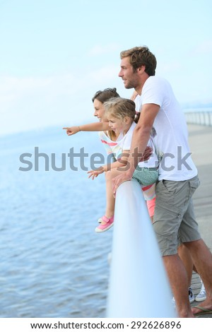 Family standing on a pontoon looking at the sea - stock photo