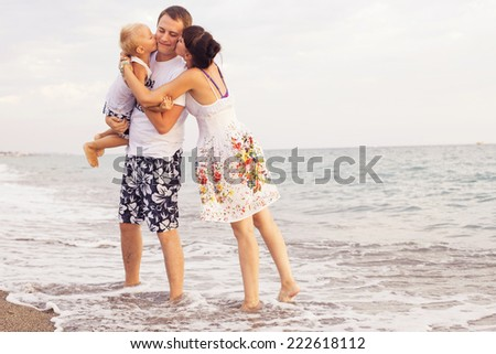 Family standing on a  sand seashore near sea looking at each other, relaxing on a vacation trip, looking on her husband. copy space - stock photo