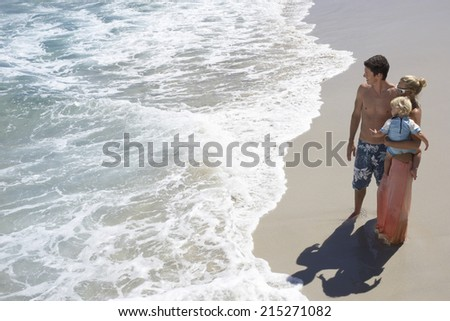 Family standing on beach beside water's edge, woman carrying daughter (2-4), elevated view - stock photo