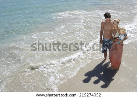 Family standing on beach in surf, woman carrying daughter (2-4), elevated view - stock photo