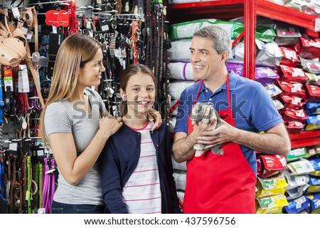 Family Standing With Salesman Holding Rabbit At Store - stock photo