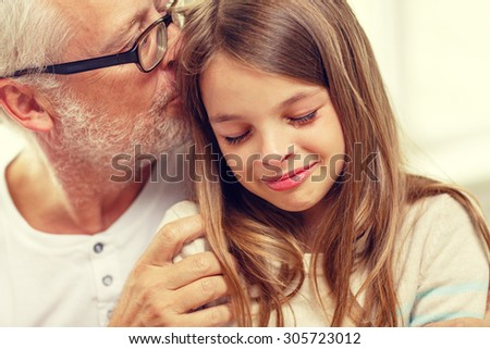 family, support, childhood and people concept - grandfather with crying granddaughter at home - stock photo