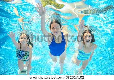 Family swims in pool under water, happy active mother and children have fun underwater, kids sport on family vacation